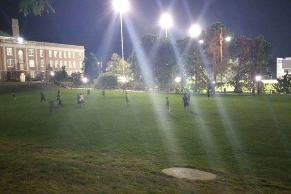 Youth play a game under the lights
