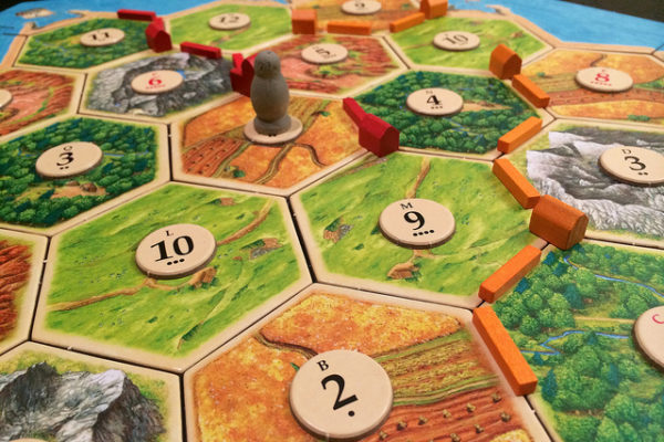 close up of settlers of catan gameboard - honeycomb shaped peices together with peices on them