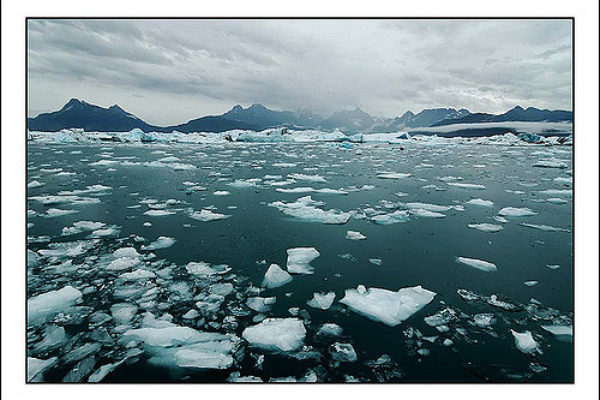 ice chunks from glacier in glacial lake with mountains in distance