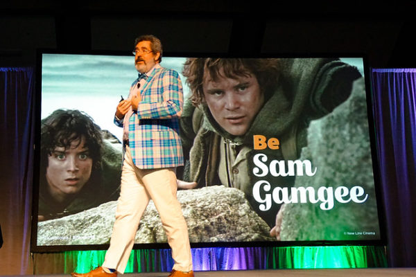 Presenter on stage in front of a slide showing an image from the movie LORD OF THE RINGS with the text BE SAM GAMGEE