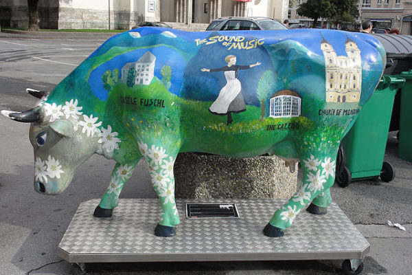 A cow statue painted with a sound of music motif.