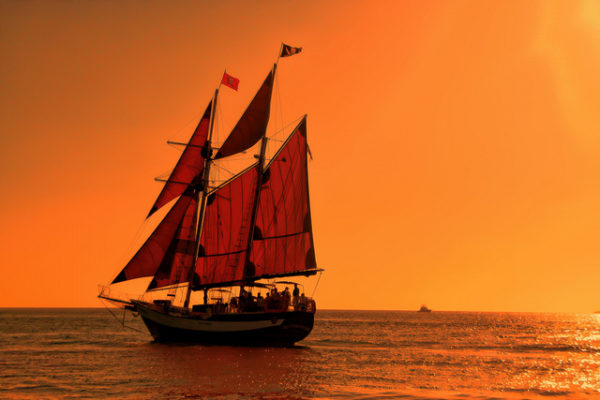 pirate ship at sea and sunset - glow of orange sky - pirate skull and crossbones flags
