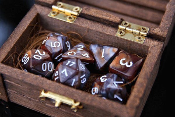 A wooden box with dice inside. The dice have different numbers of sides, from 20 to 4