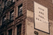 Sign on the side of a building that says: How are you really?